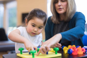 Woman working with child on puzzle